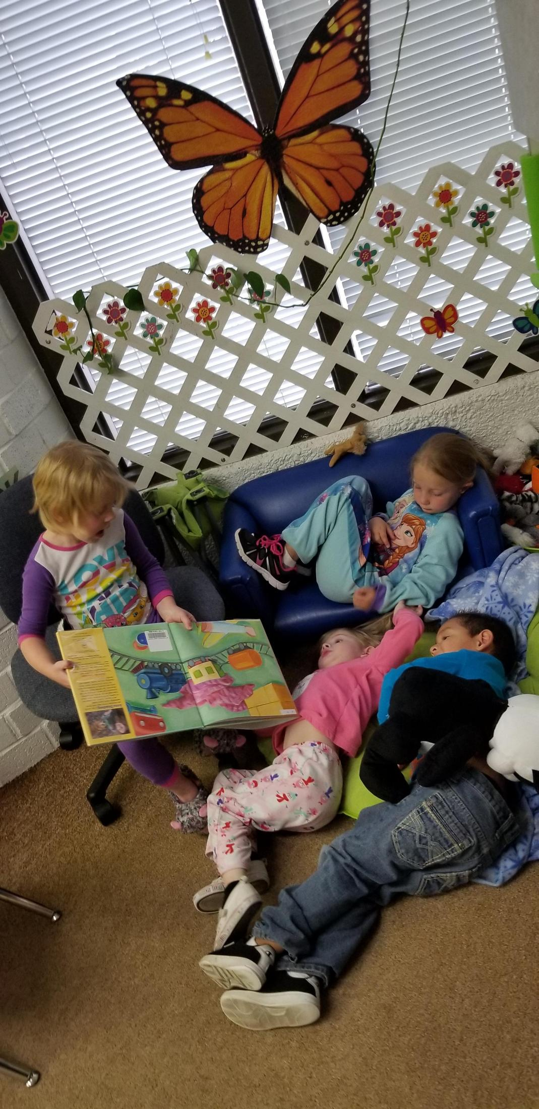 Girl reading to classmates in library