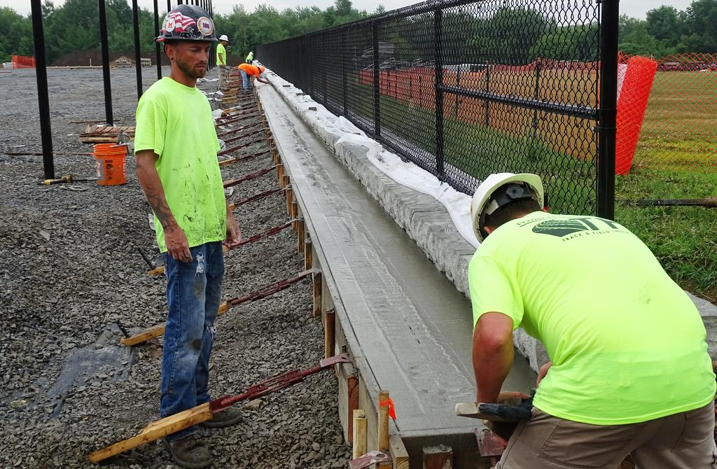 Pictured early in the morning of Wednesday, July 17, 2019 at the southern wall of the future pickleball & tennis courts on the athletics field area are construction workers engaged with smoothing cement that was poured a short while ago that morning.