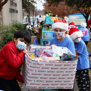 dyer students work together to carry box full of toys