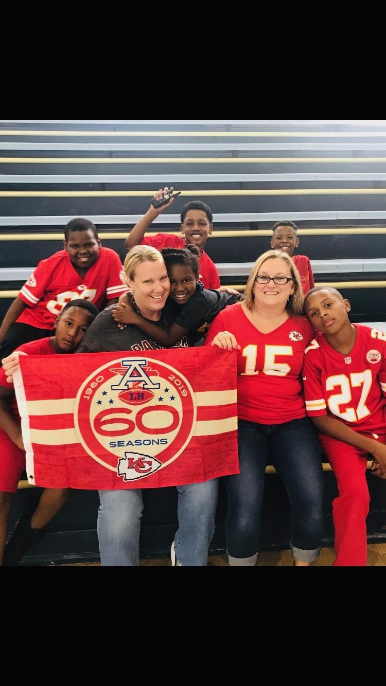 teachers with students in chiefs red
