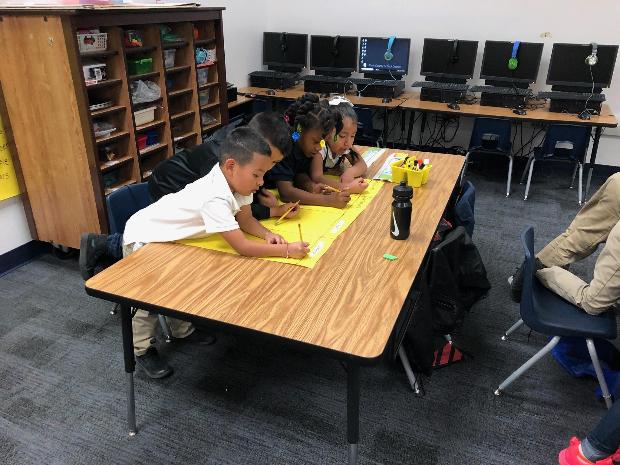 4 first grade students writing on yellow chart paper