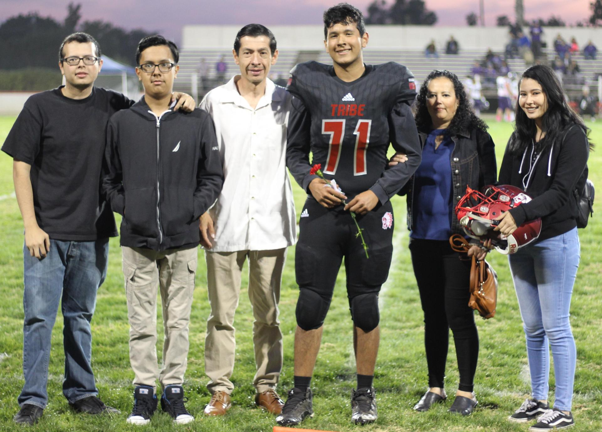 Senior football player Andres Martinez and his escorts.