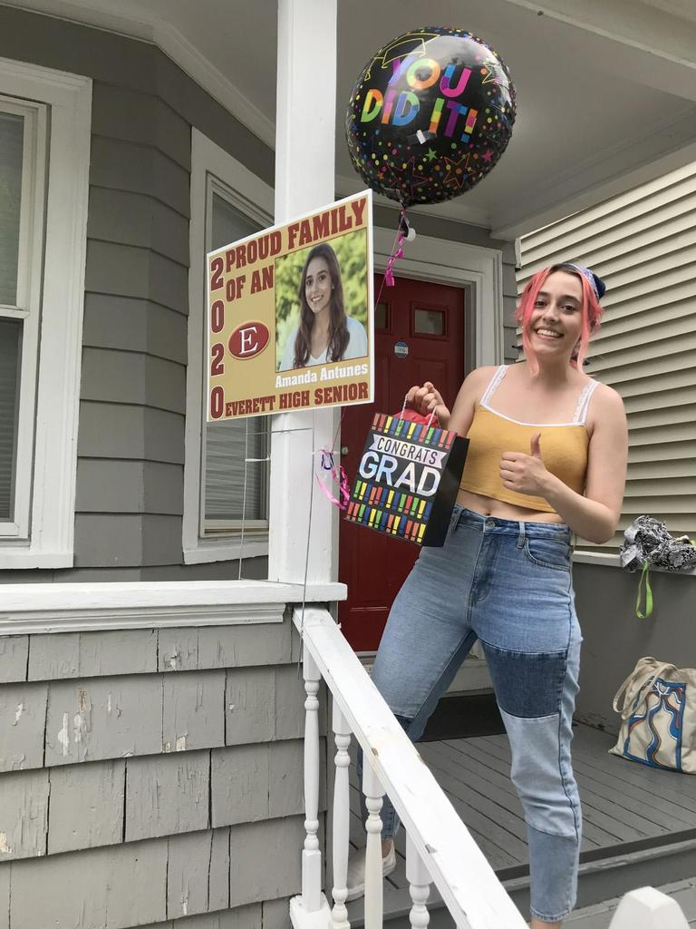 A student on her front steps, with a ballon, a sign, and holding a gift bag