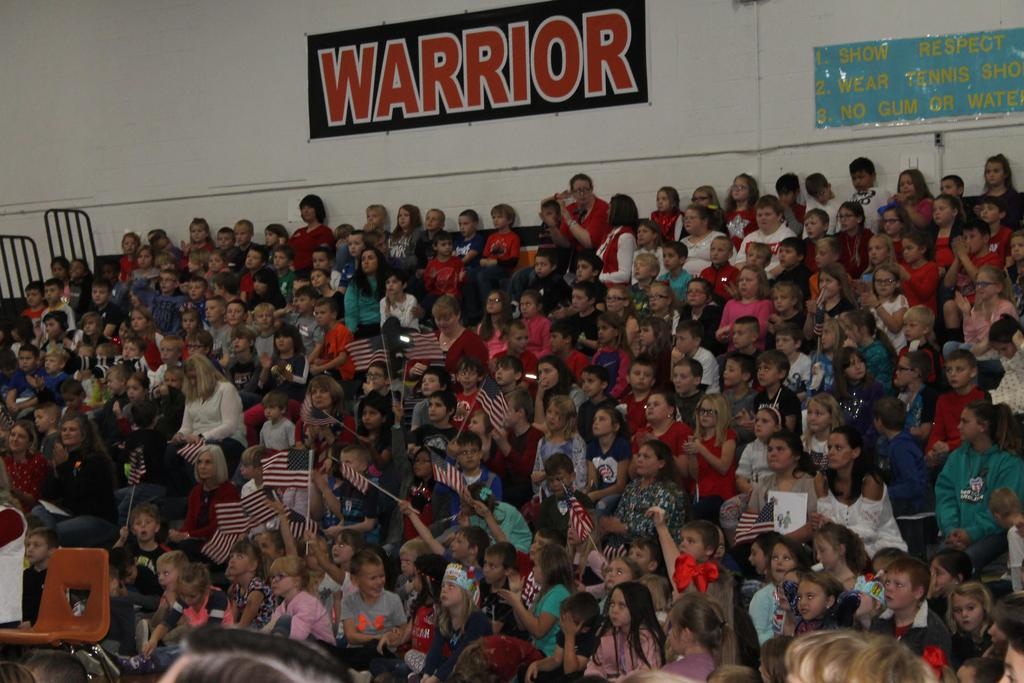 Students gathered in the gym waving flags during Veterans Day Assembly