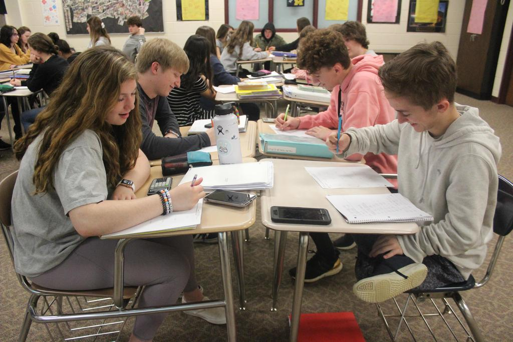Four students sitting at desks working on math problems.