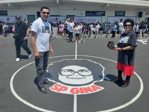 Mr. Cruz and Ms. Wright stand next to centerpiece of basketball court featuring SP Gina's face