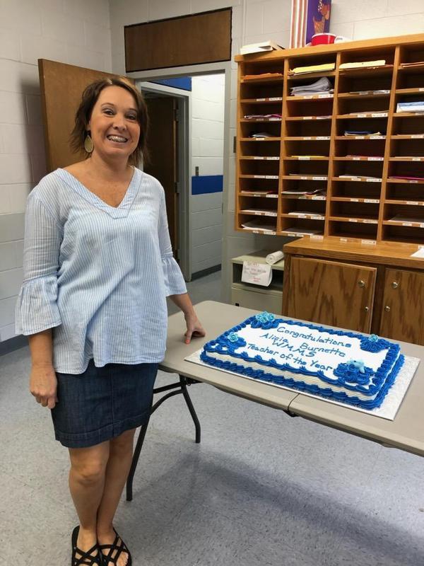 Mrs. Burnette standing beside of cake.
