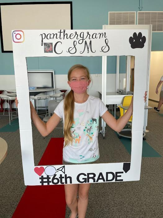 Student holding a frame that says welcome to 6th grade!