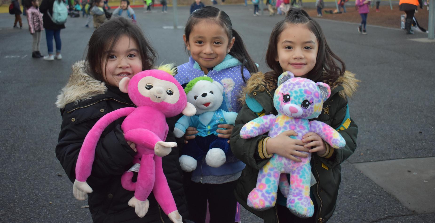Three girls holding their stuffed animals, smiling!