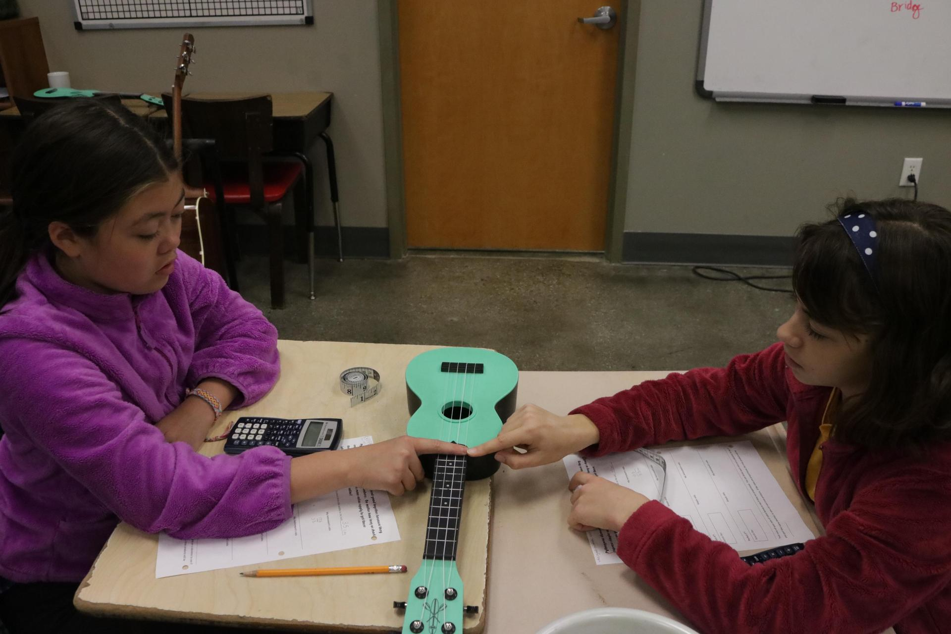 Students study the proportions of a guitar