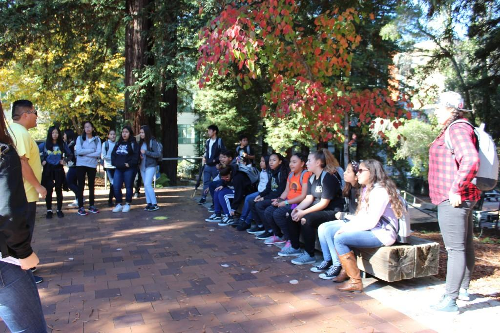 several students sitting on a log bench or standing while listing to a tour guide