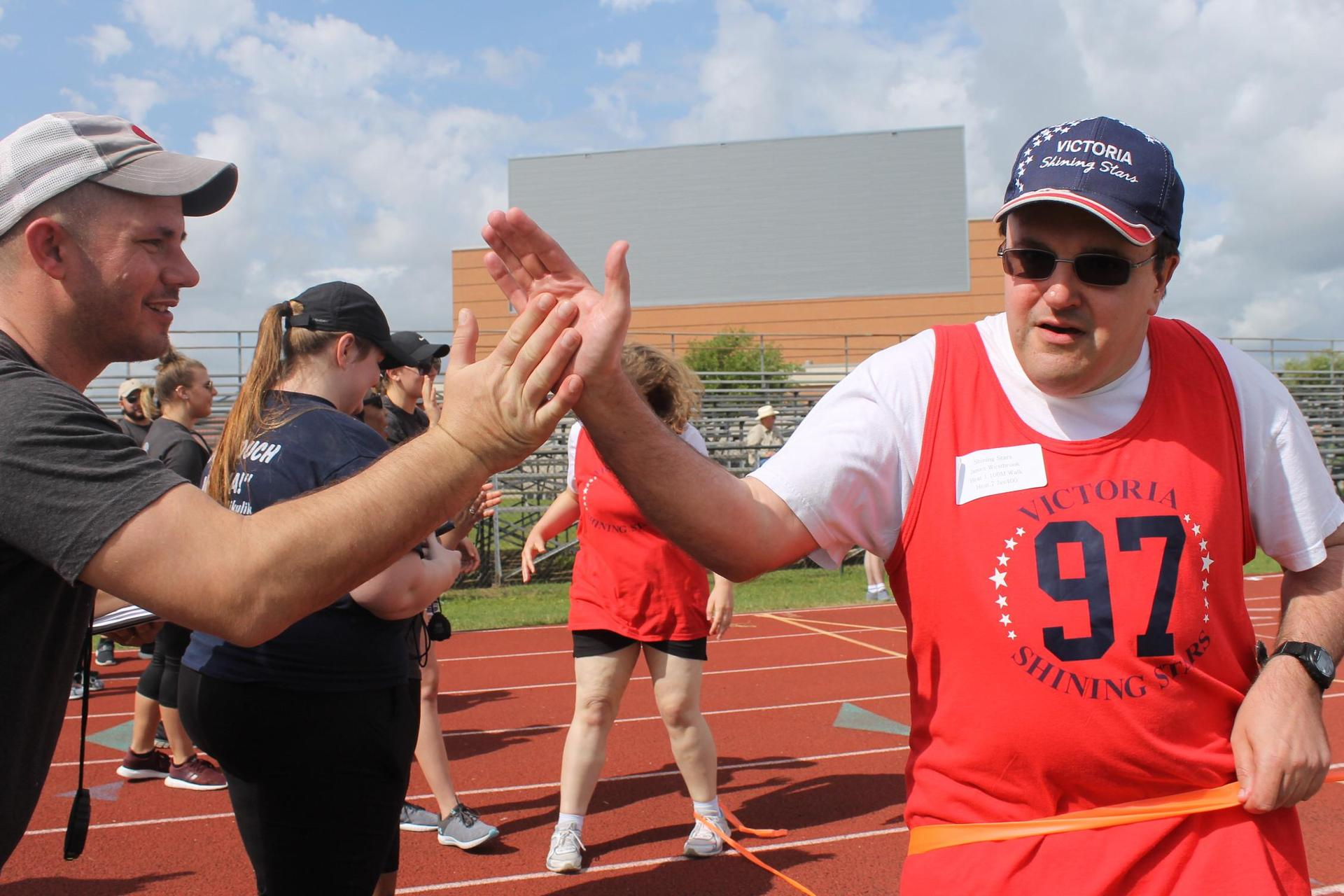 man high fiving a volunteer at the finish line