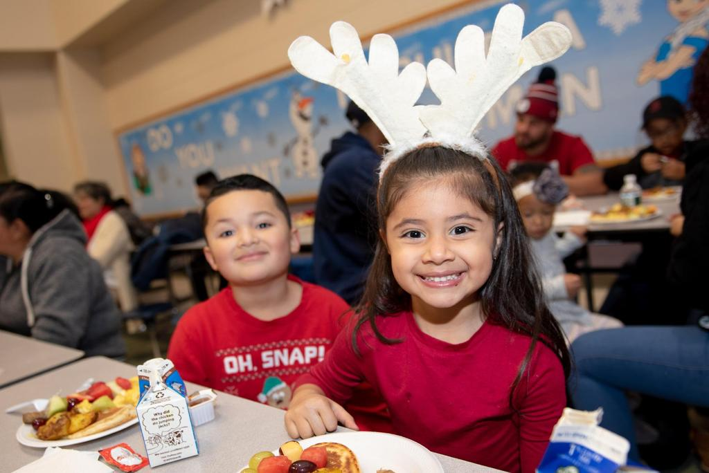 Two students, a boy and a girl who's sporting Reindeer antlers, at a cafeteria table