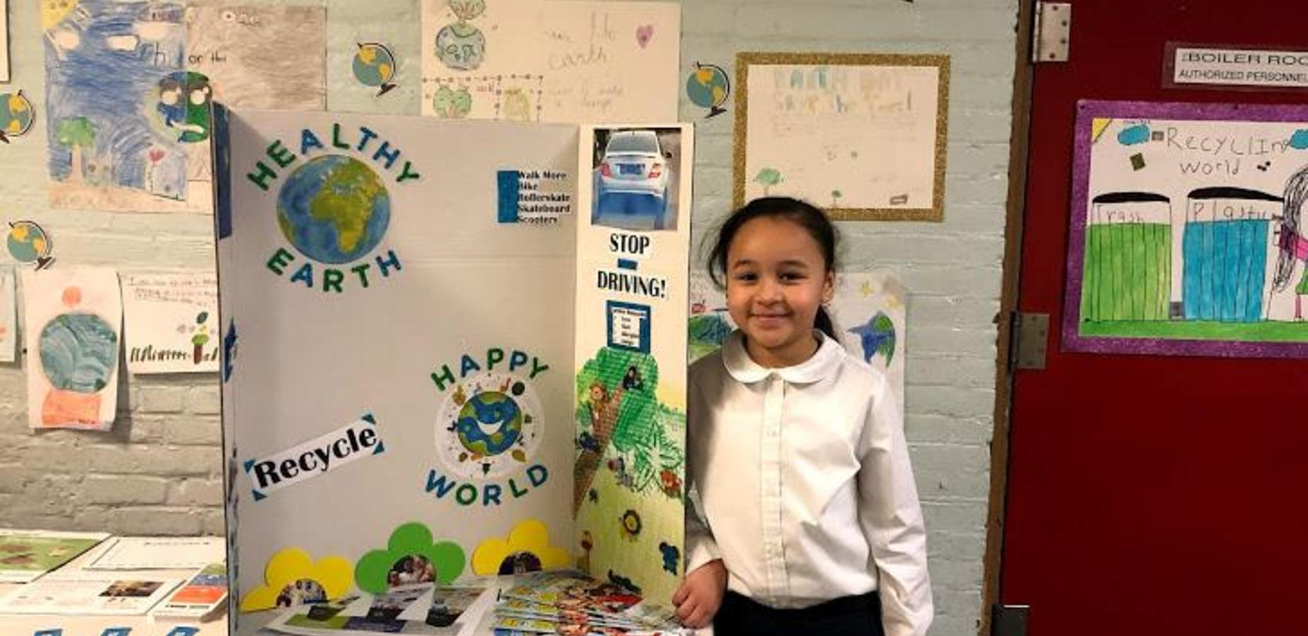 Student standing to the left of her Earth Day Poster