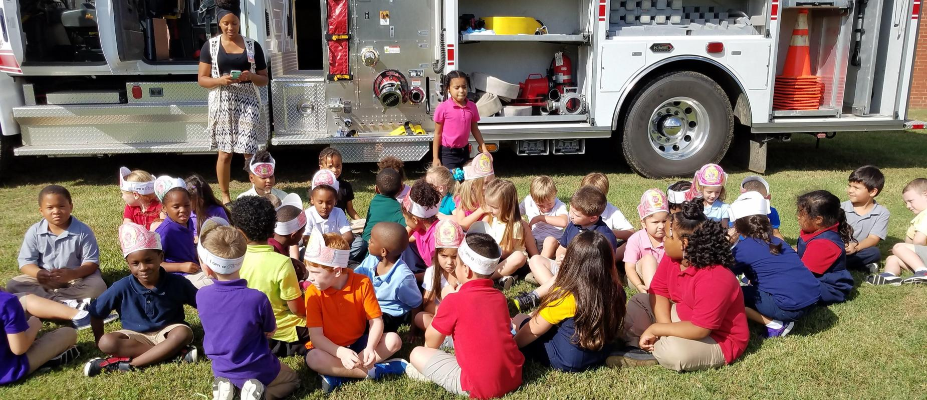 students sitting in grass in front of a fire truck