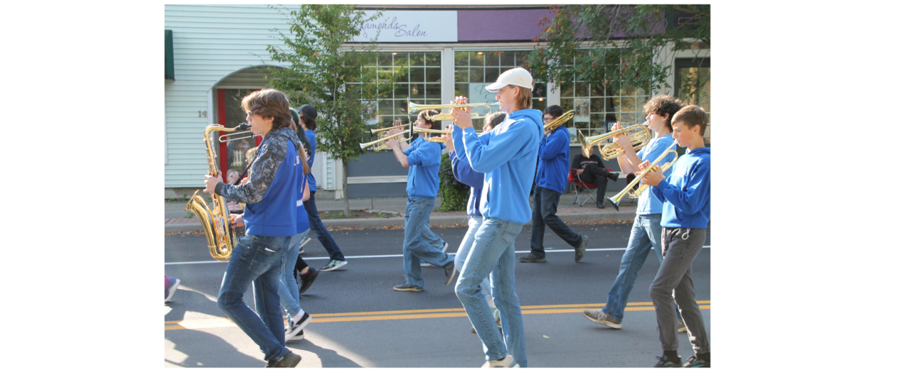 students marching playing trumpets and saxaphones