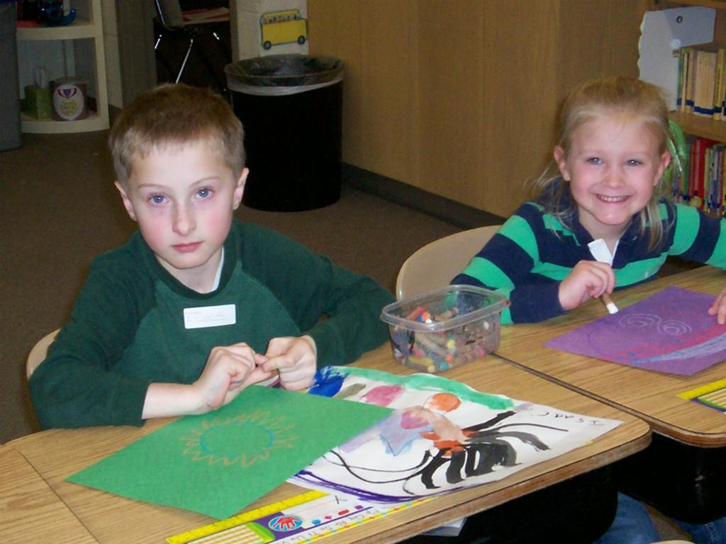 two students look at camera while coloring