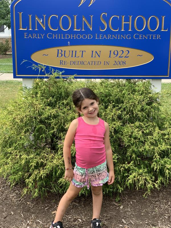 Photo of kindergartner in front of Lincoln School sign