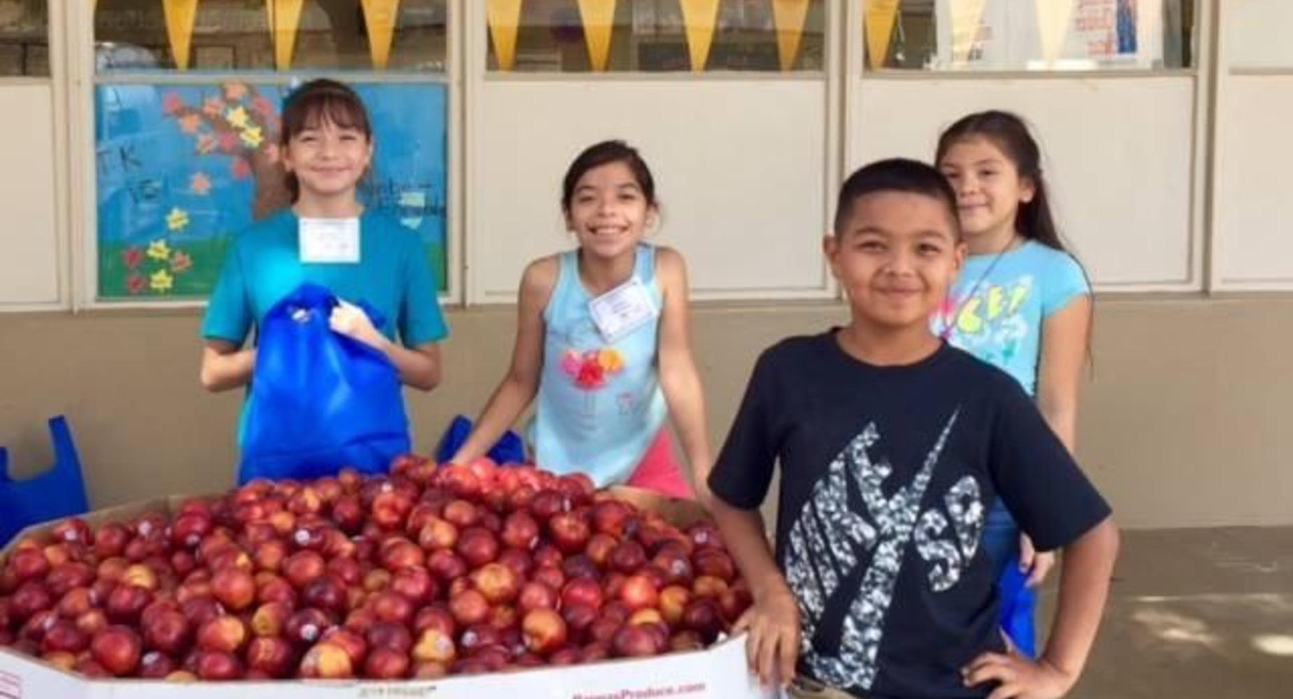4 students selling produce during Farmer's Market.
