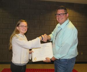 Emma VanSprange accepts a certificate of honor from High School Principal Tony Petersen.