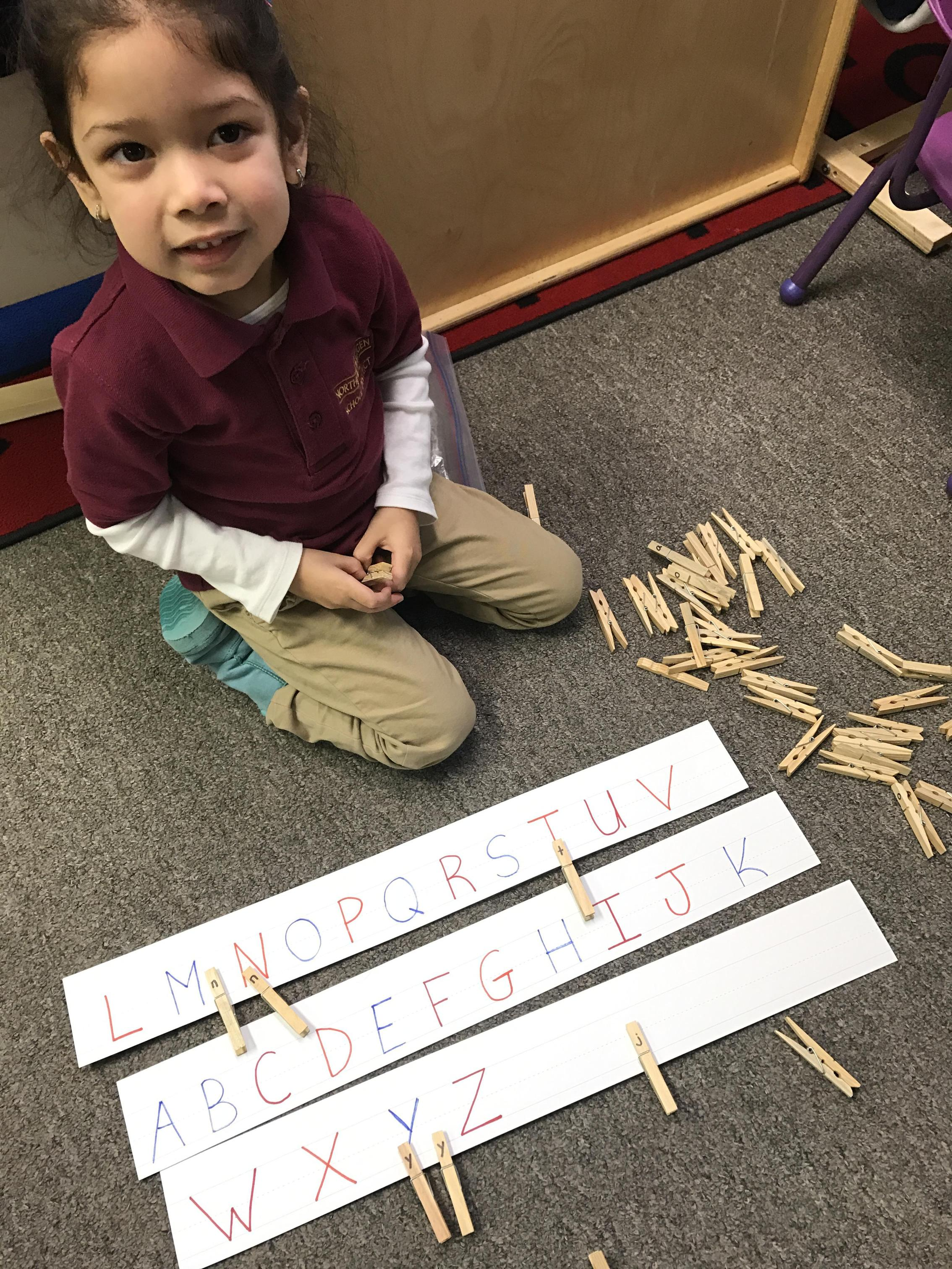 Student working on a letter matching game created by her teacher