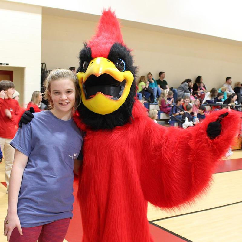 Student poses with cardinal mascot.