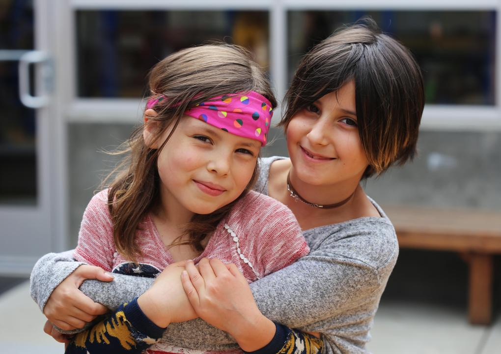 A girl with short dark brown hair wearing a grey, long-sleeved shirt hugs a girl with shoulder-length medium brown hair wearing a bright pink bandana around her head. They are both looking at the camera.