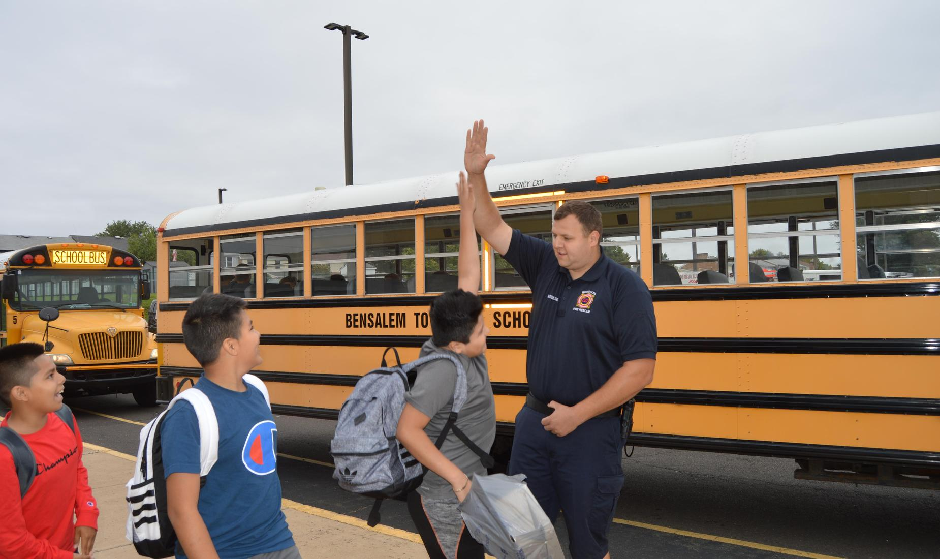 Bensalem Fire Rescue member high-fives a boy as two other boys look on