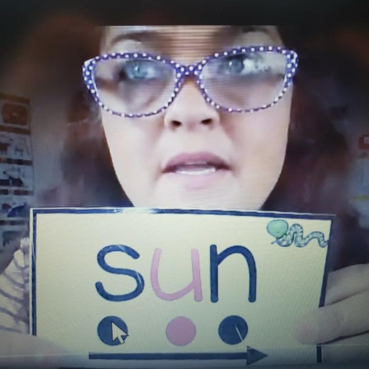 A teacher holds up the word 'sun'