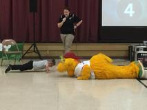 Student with Altoona Curve mascot Loco doing push ups