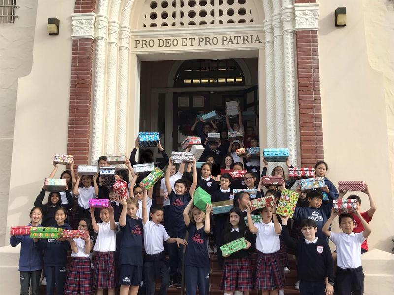 6th Grade wraps gifts to donate to Catholic Charities Thumbnail Image