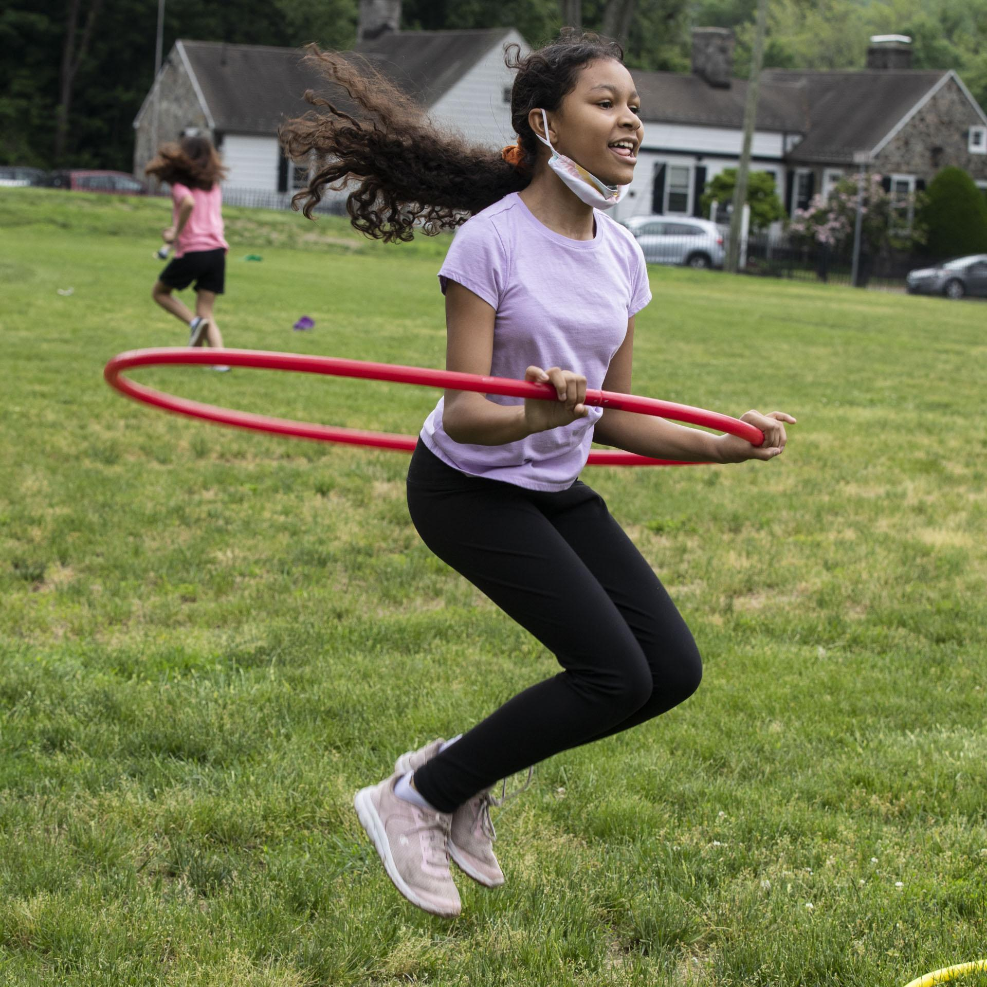 Student jumping with hula hoop
