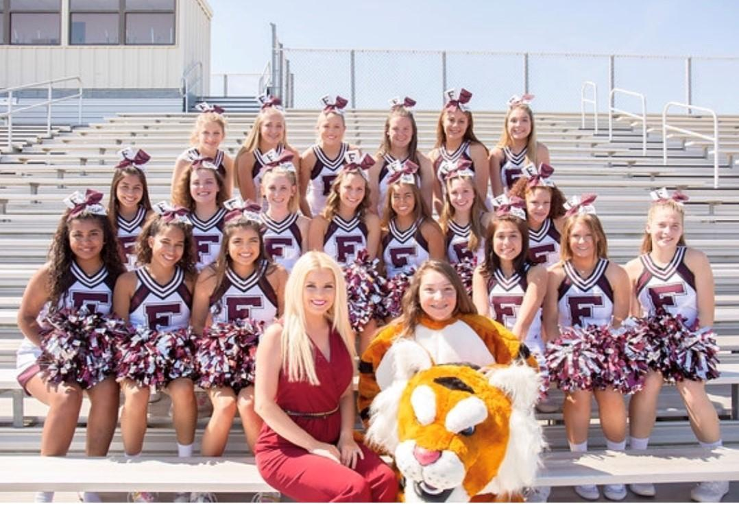 FHS Varsity & JV Cheerleaders,  Mascot, and coach smile and pose for a picture in the stands.