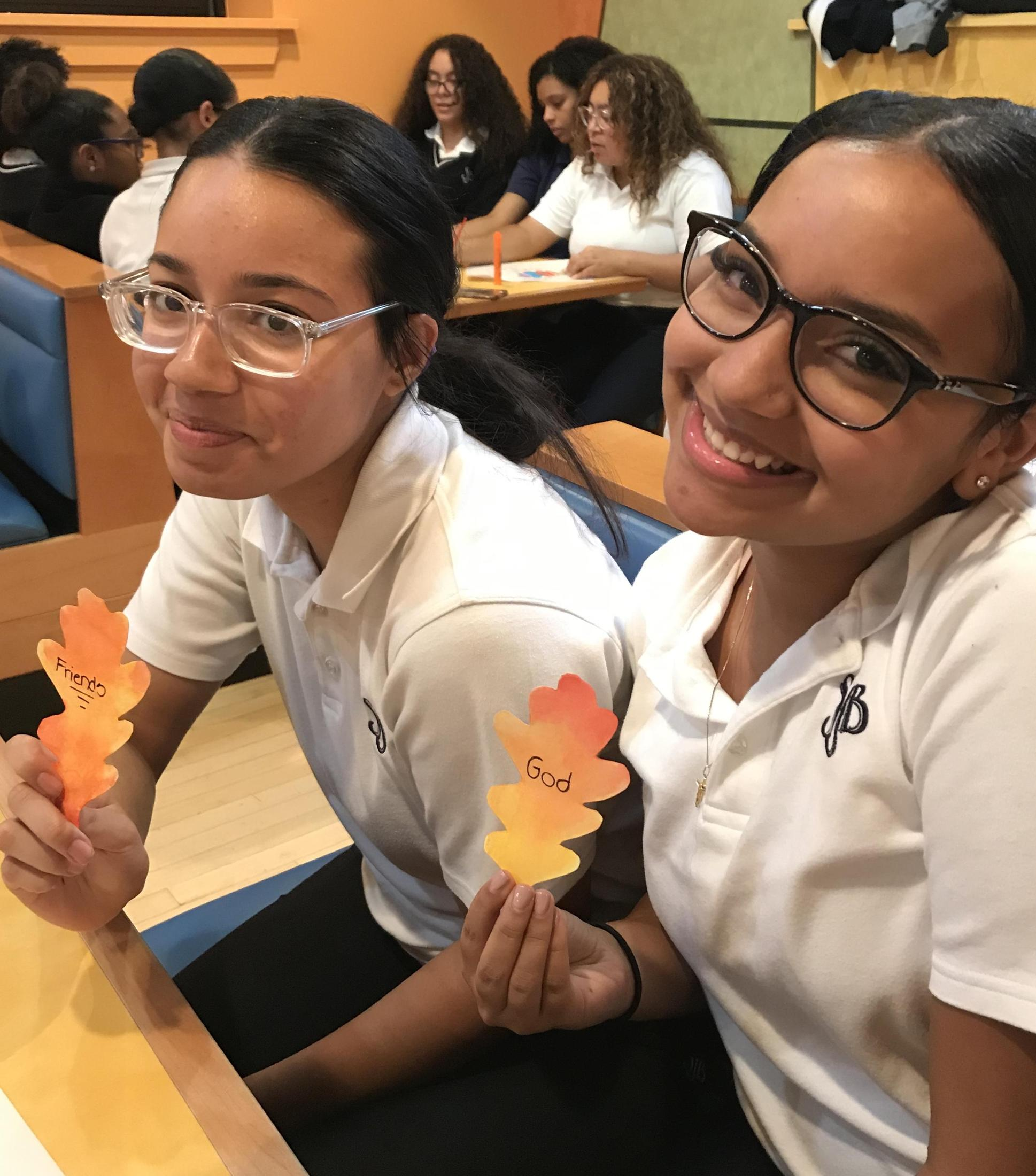 two girls hold painted leaves