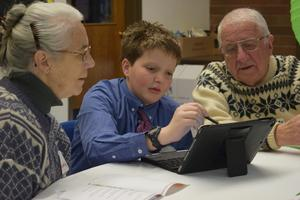 grandparents flanking boy who is pointing to an iPad on a table in front of them