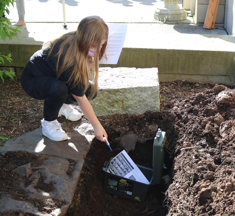 Elizabeth Giustiniani, a 6th grader at Roosevelt Intermediate School, places a thermometer in a time capsule on May 7 as part of a social studies project.