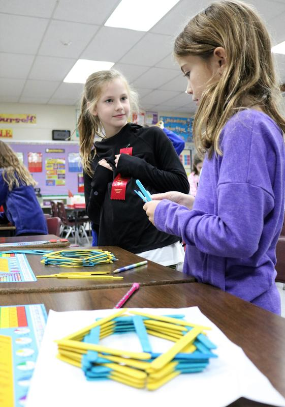"Photo of:  Washington 3rd grader Darby Revock (left) consults with classmate Emma O'Brien as they use colored popsicle sticks to build ""Factor Forts"" in Lisa Bukowsky's class."