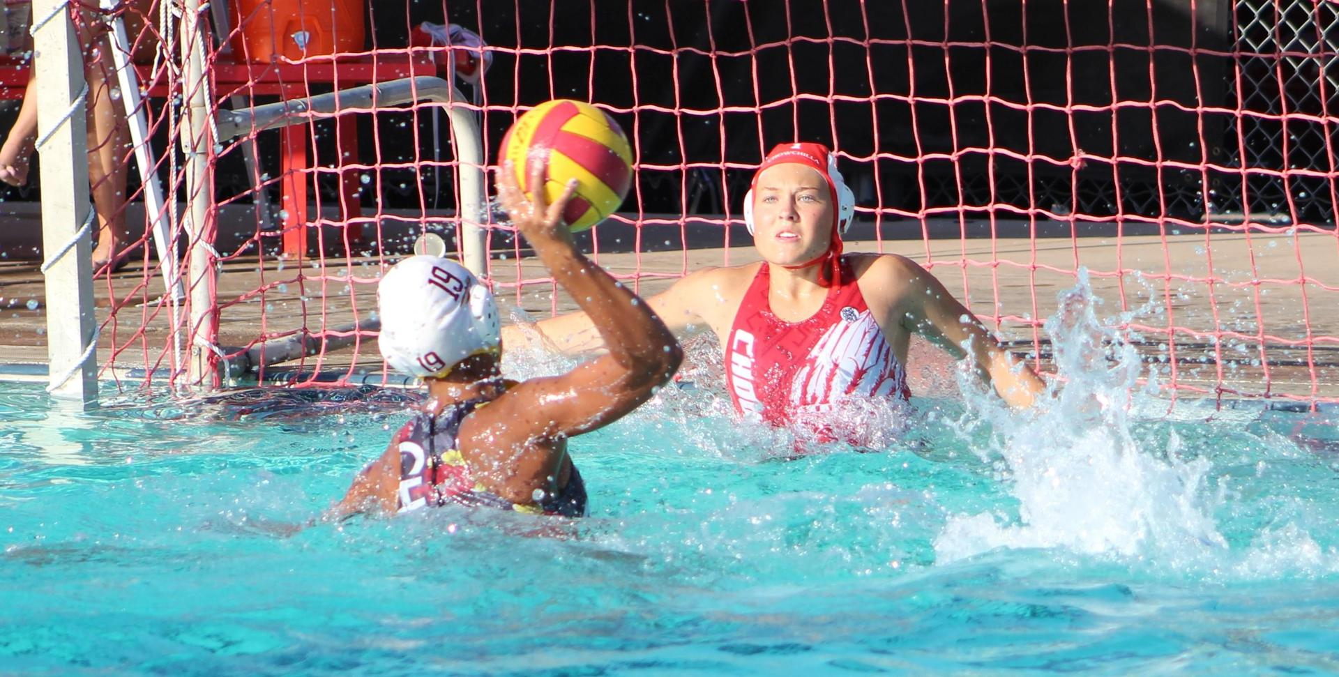 girls water polo player about to block a goal