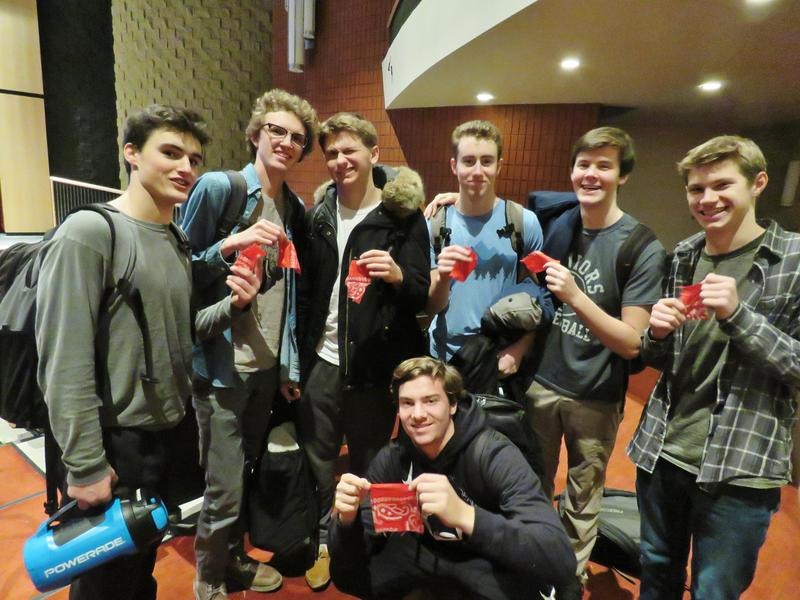 A group of TKHS students show their pieces of a red bandana they recieved as part of the