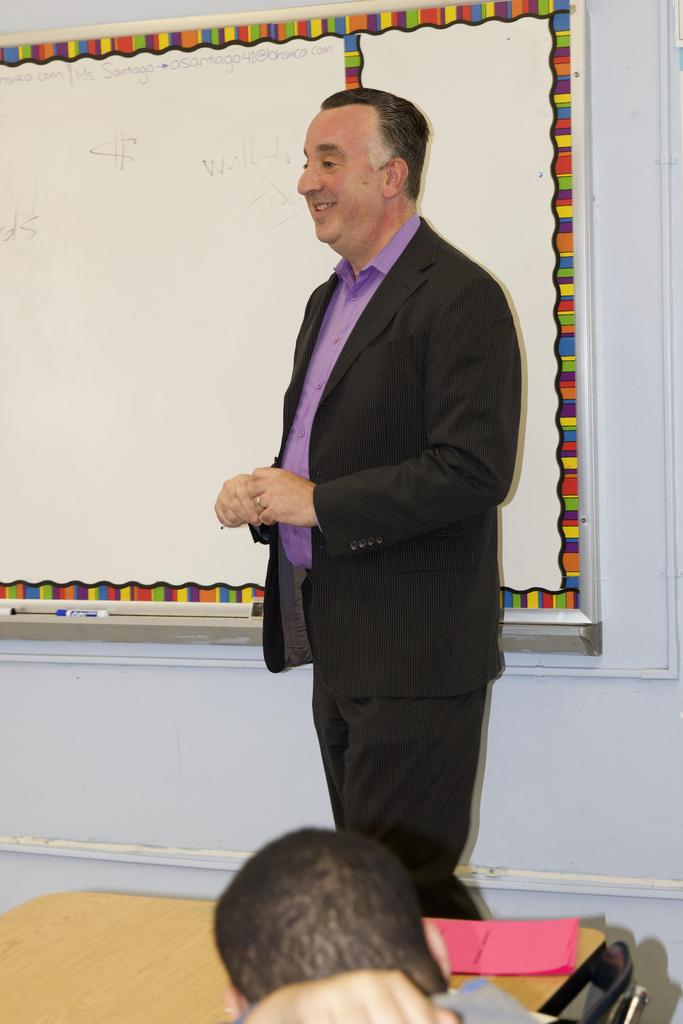 a suited man smiling in front of a whiteboard