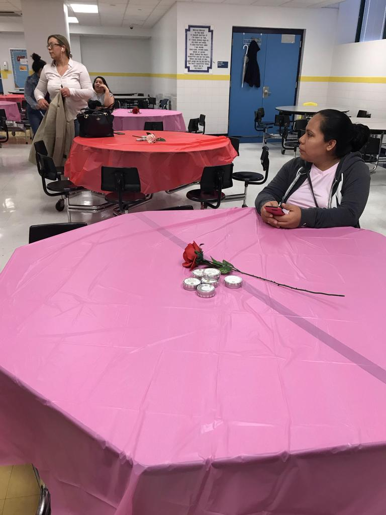 mother seated at table with a pink table cloth & a red rose