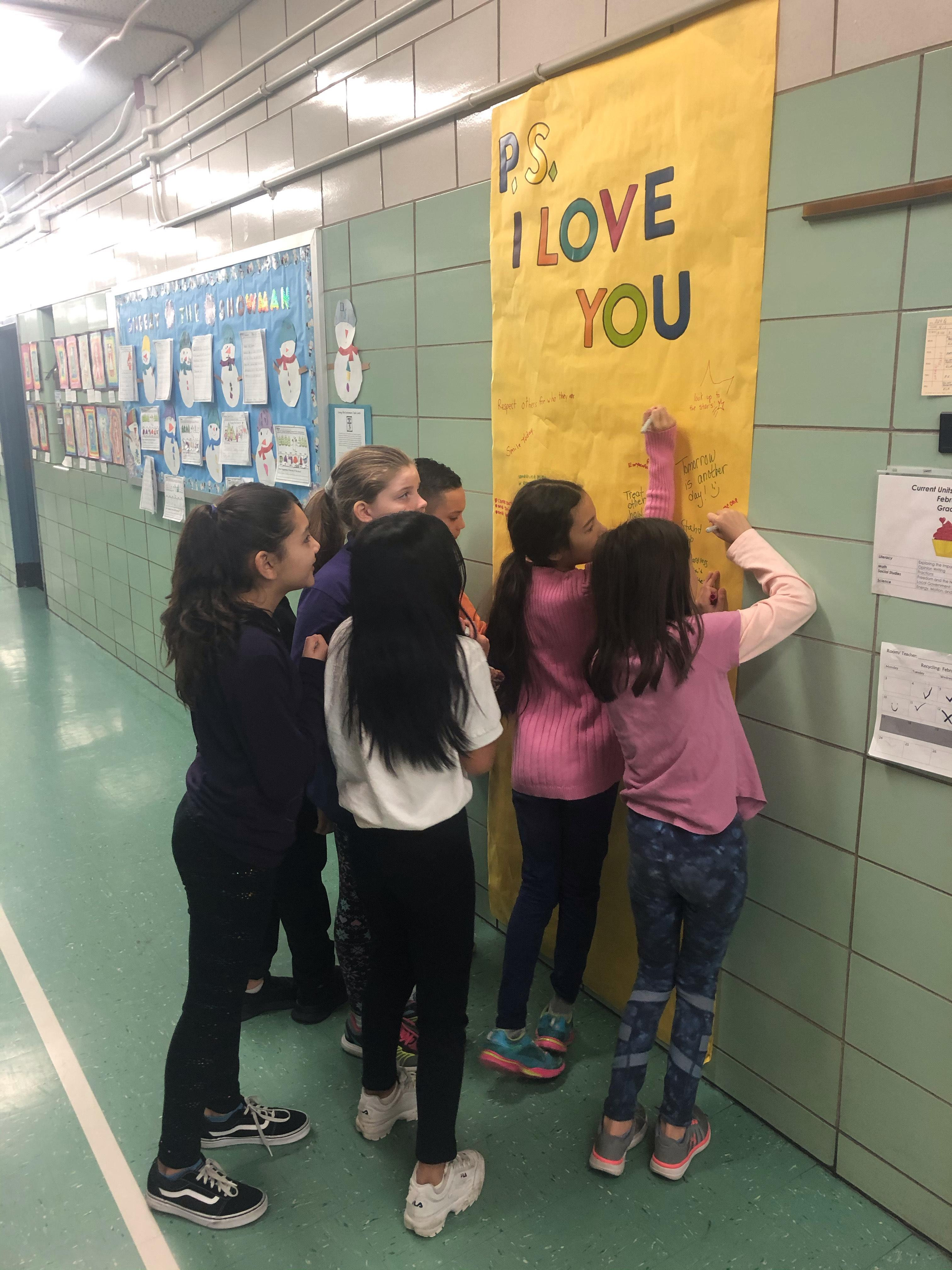 students in school hallway writing messages of support on butcher paper for PS I Love You Day