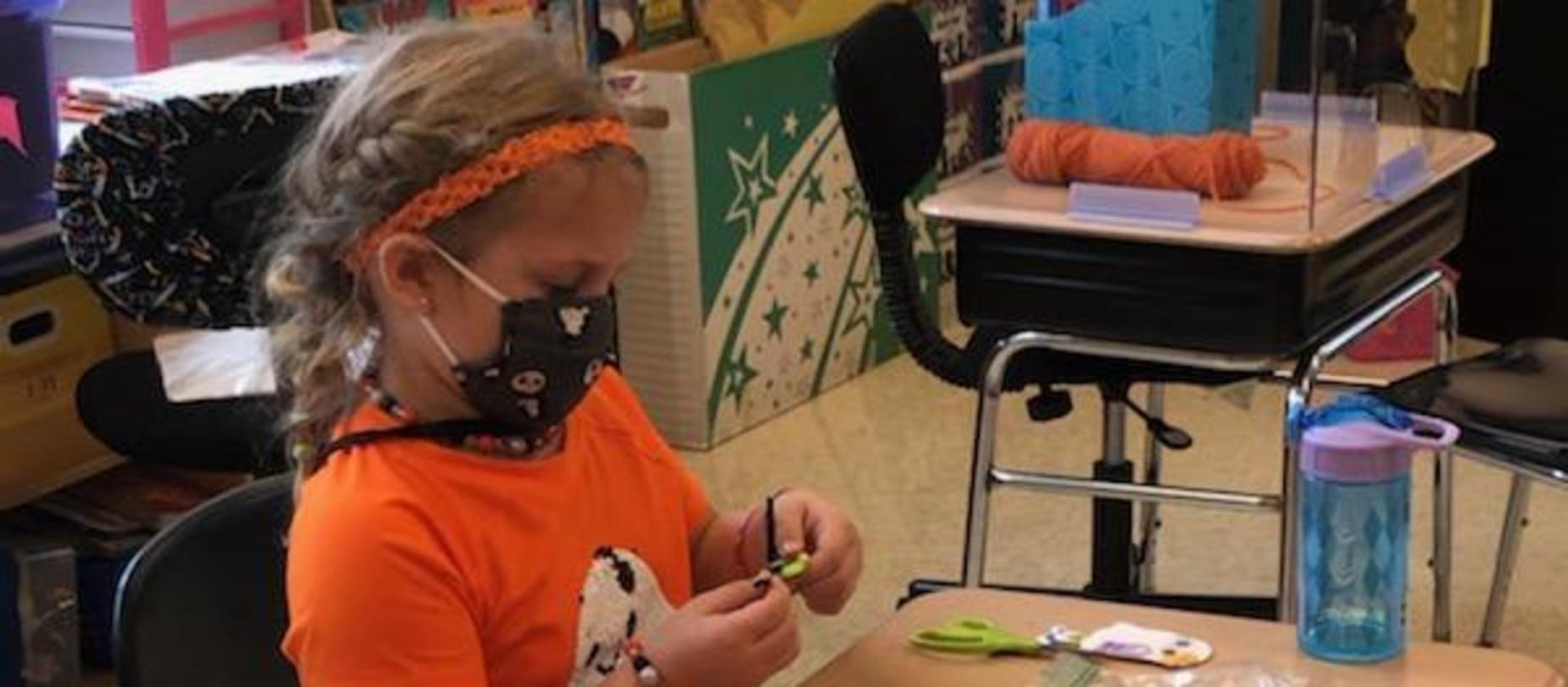 student making halloween crafts