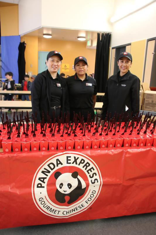 3 Panda Express workers in front of the lunches provided for the students.