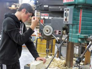 Using a drill press, the students bore out holes for the holders.