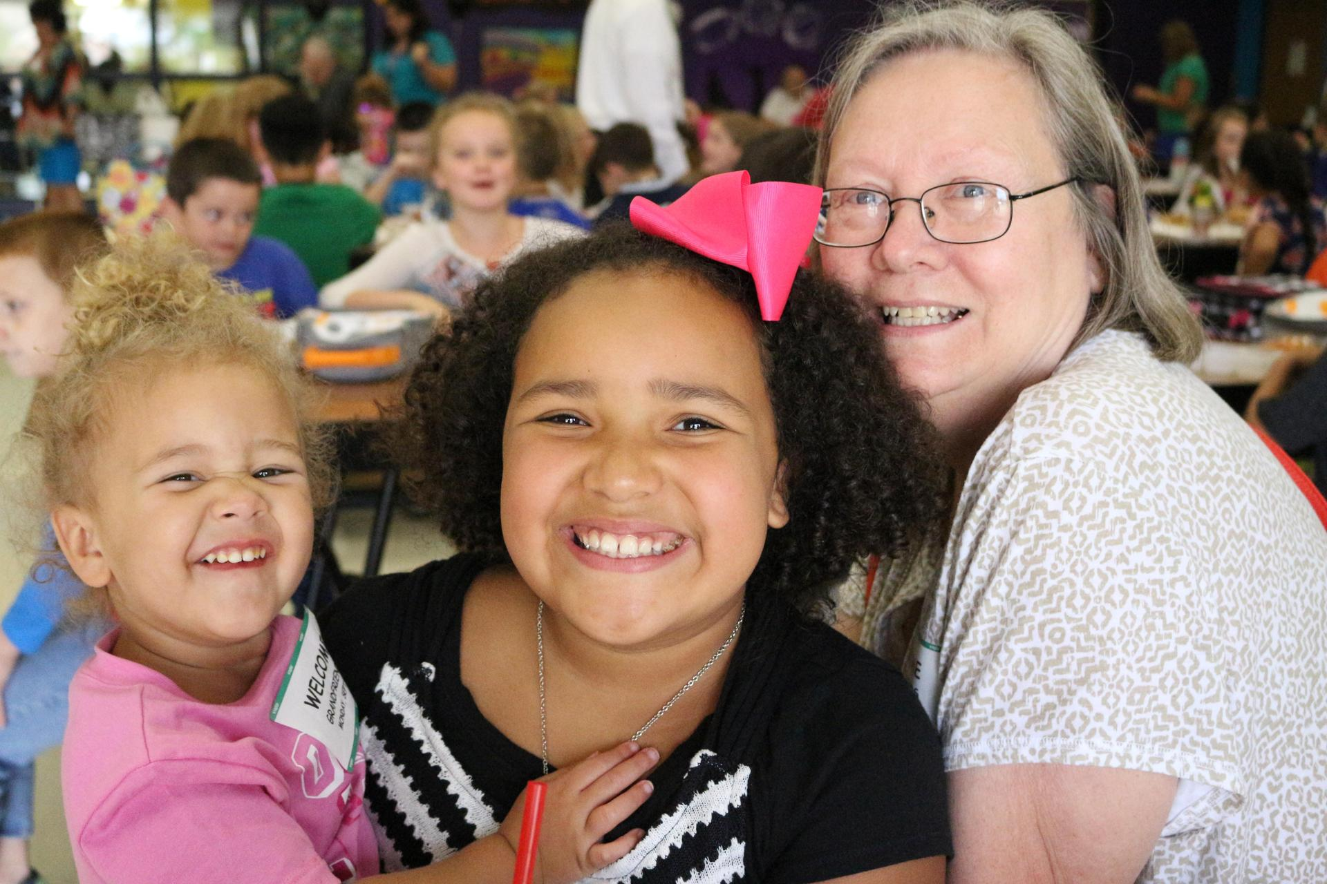 grandmother poses with 2 young granddaughters