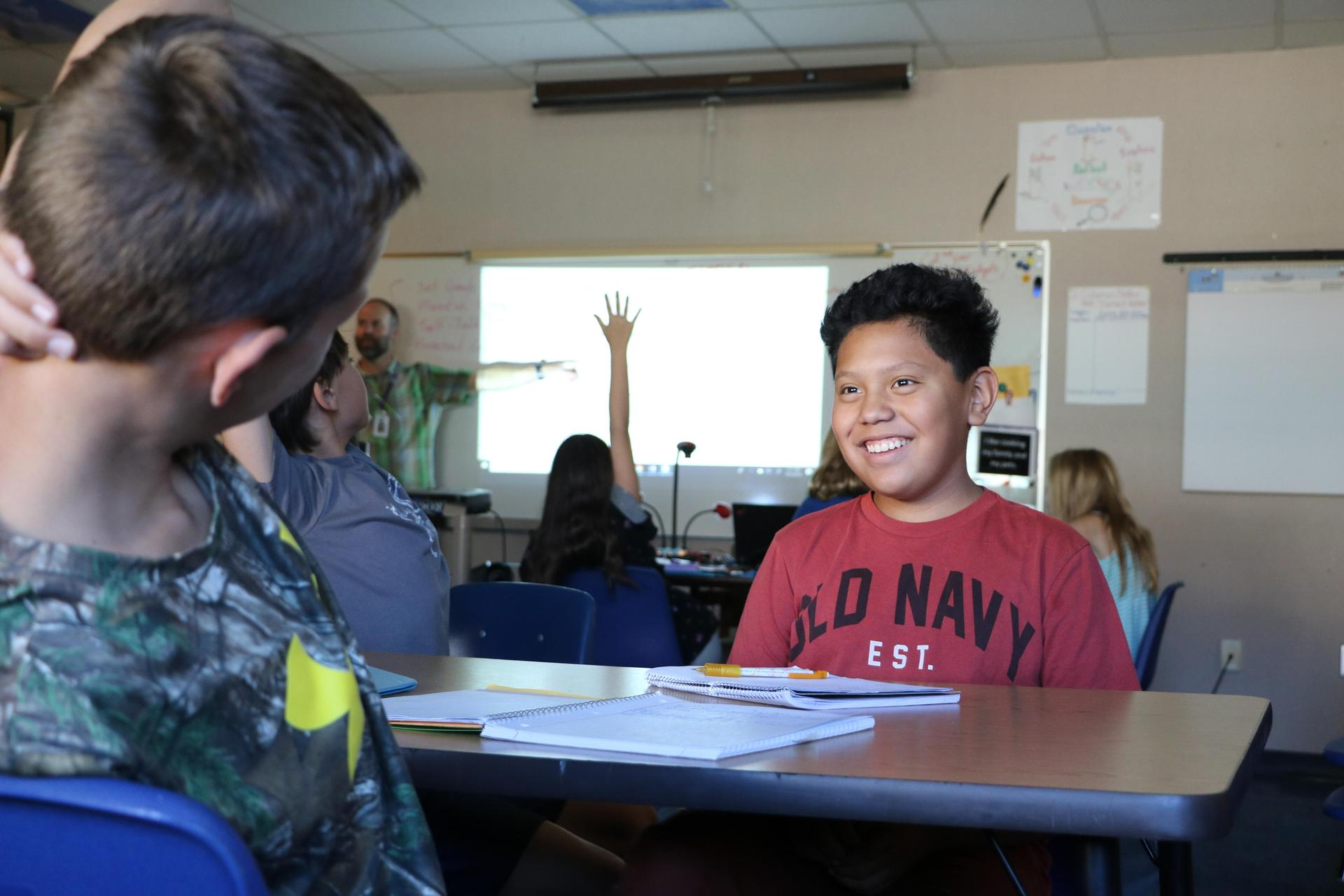 A student smiles broadly at a classmate.