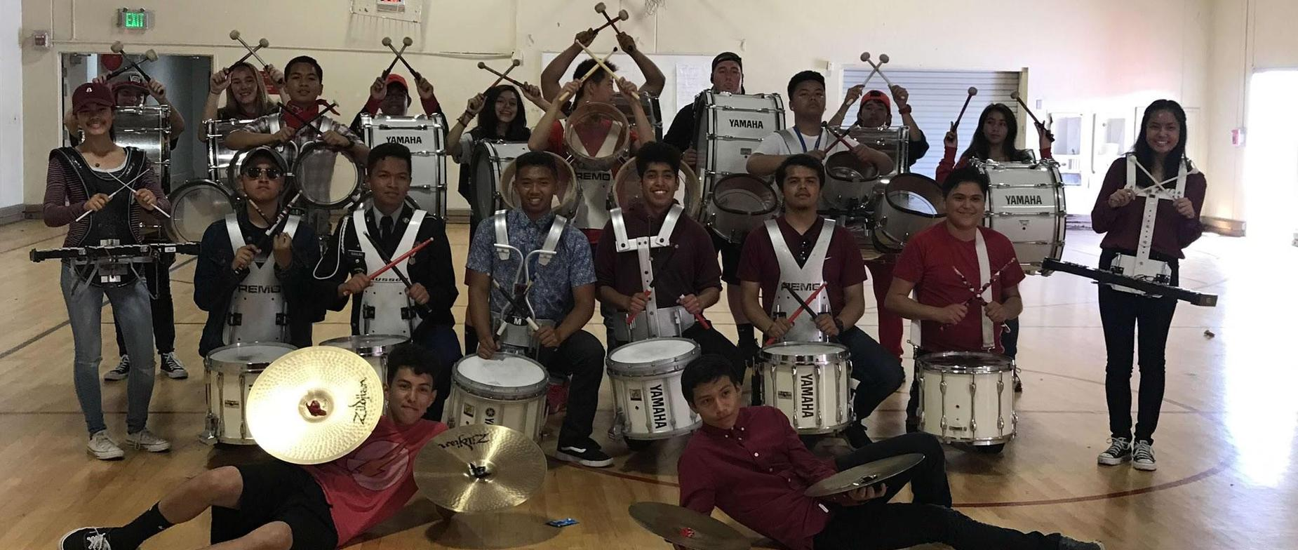 about 30 Seaside High School drum line students both male and female posing for a picture with their drum line gear
