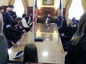 Skyview students sit at a table in the Governor's ceremonial office while they visit with him and ask questions.