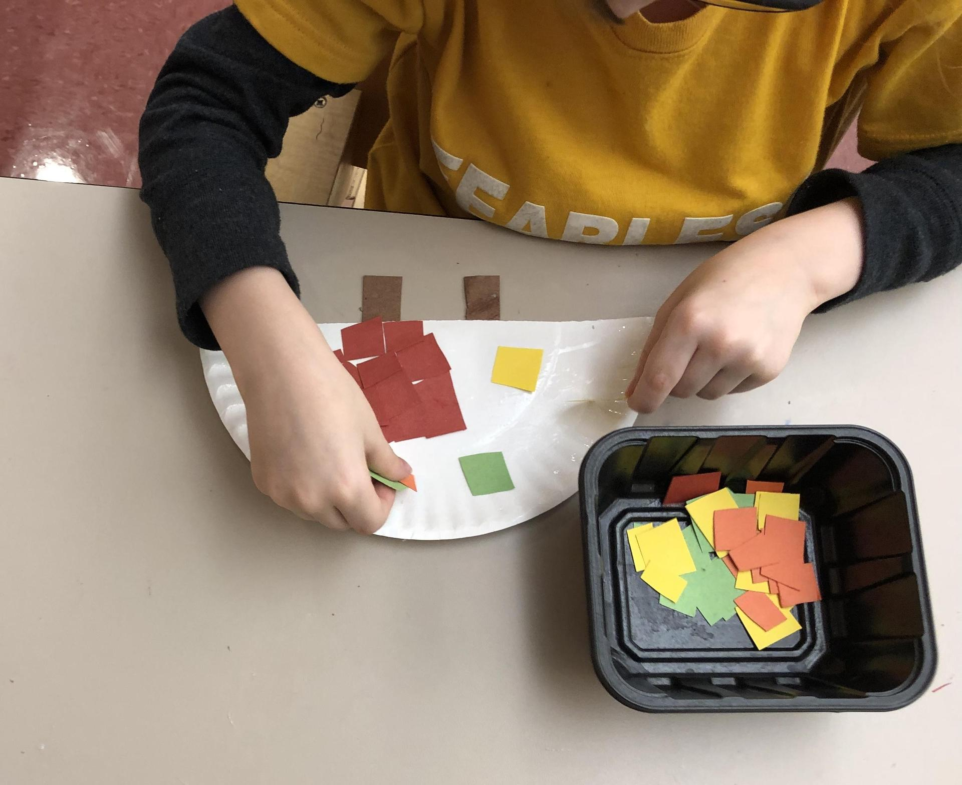 Gluing small pieces of paper to make a turkey.